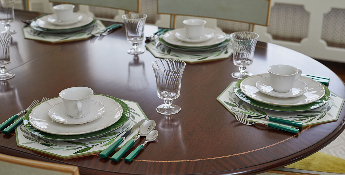 Dining room table set with teacups, plates, and silverware
