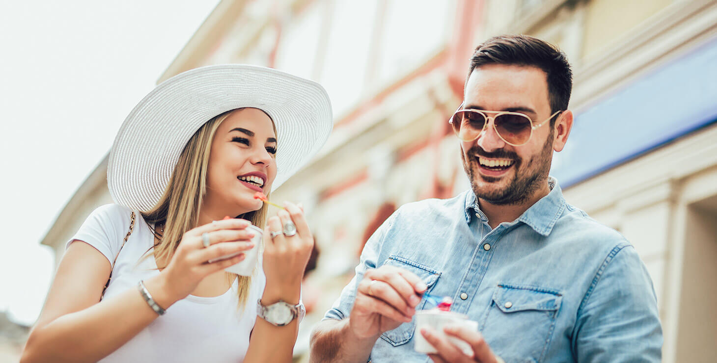 Couple having fun and eating a treat while shopping
