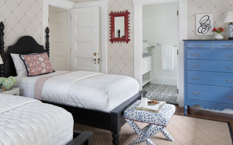 Room with two twin beds a blue dresser and a private bathroom