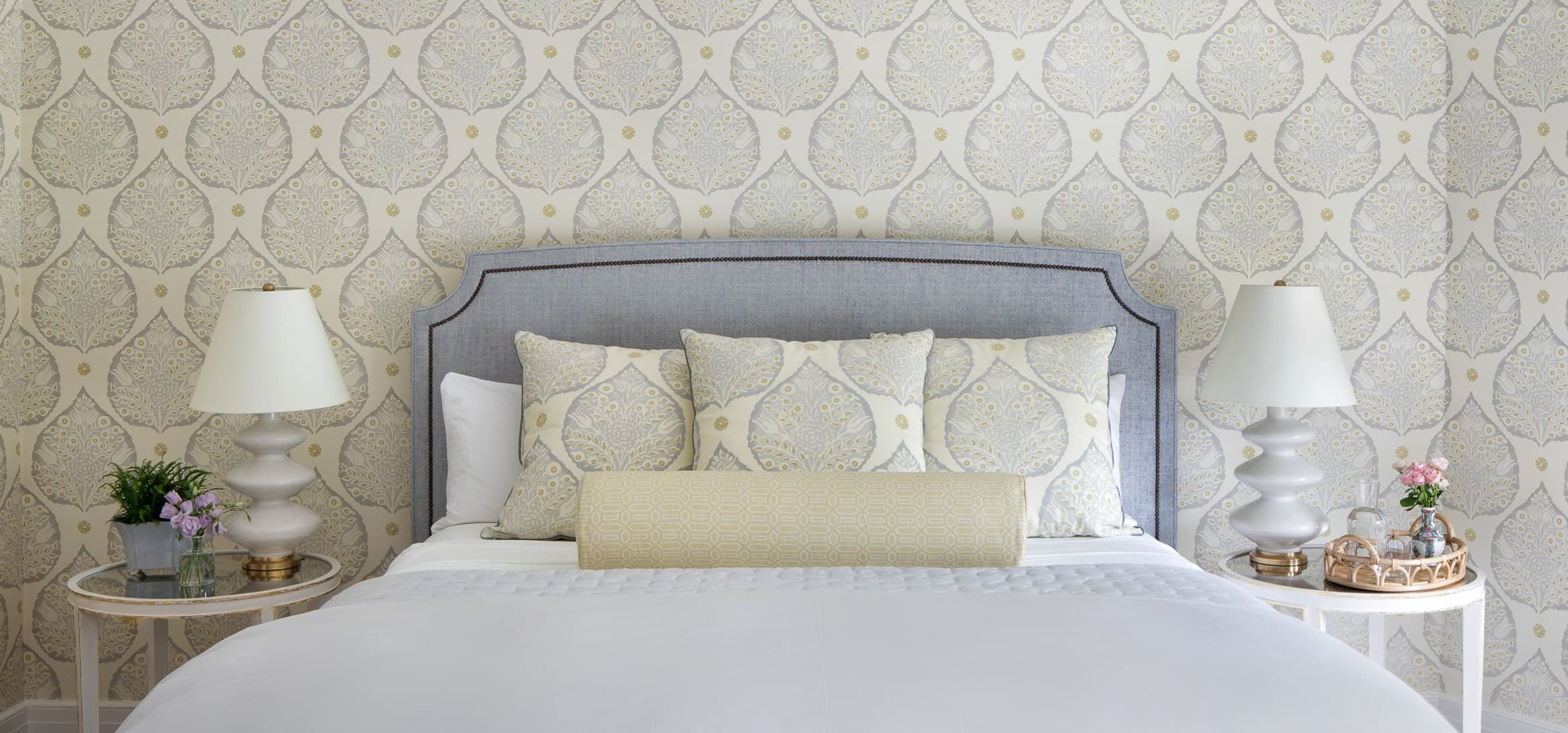 Room with a king bed and two matching end tables and lamps with a floral leaf wallpaper and matching pillows