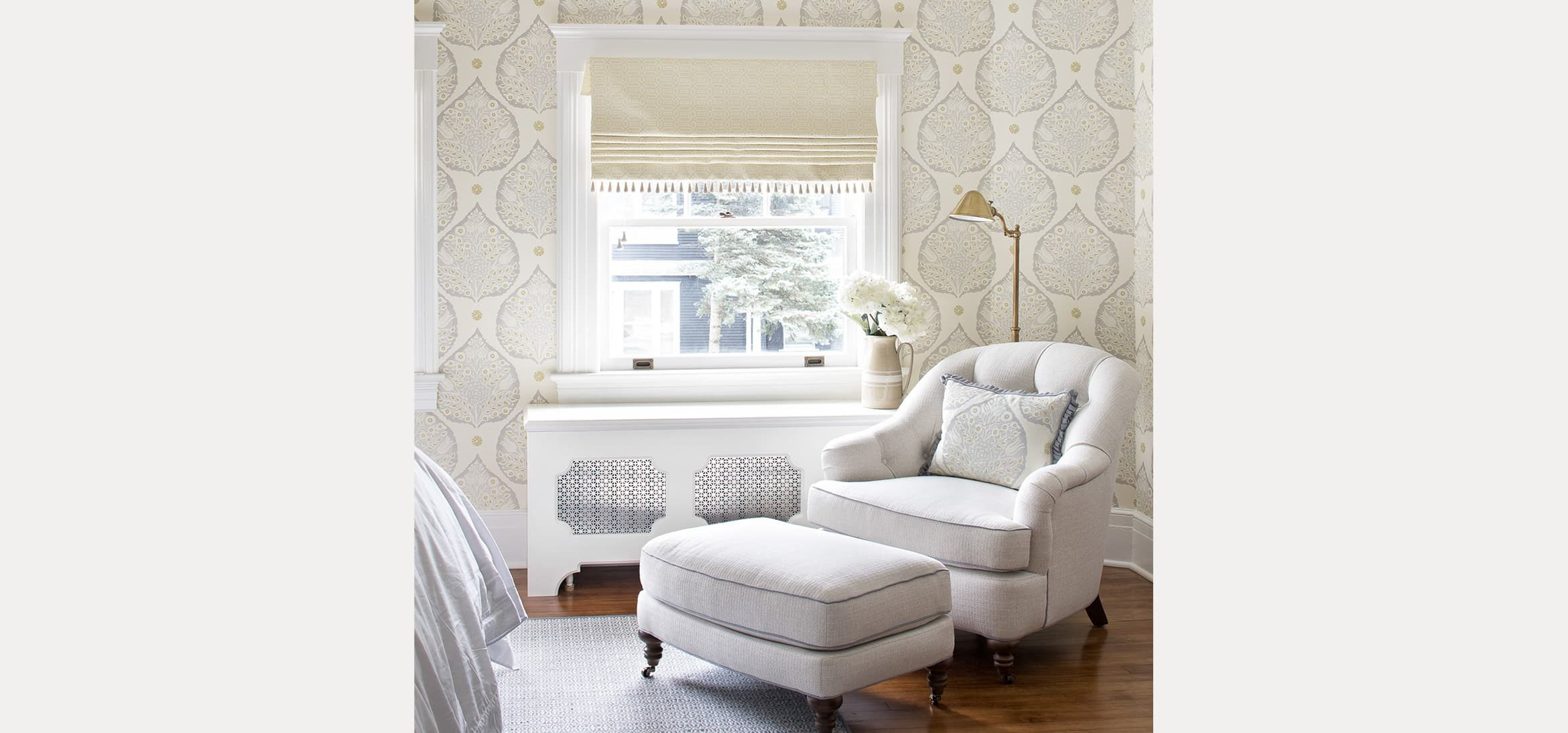 Room with a seating area and foot stool with a leaf motif wallpaper