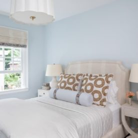 Bed in a room with light blue walls and two end tables with matching lamps