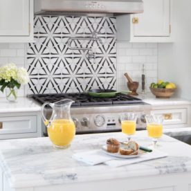 Kitchen with white marble countertops with a pitcher and two glasses of orange juice and a breakfast muffin