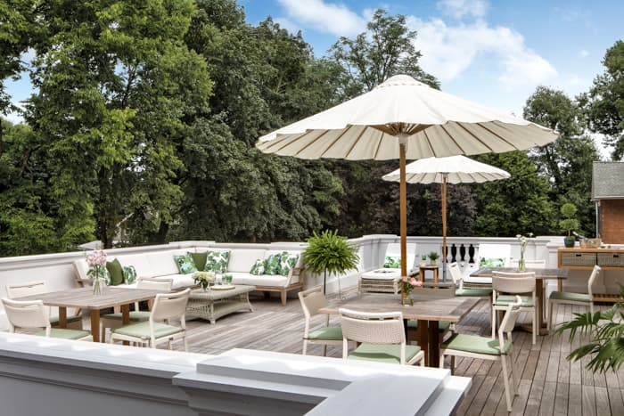 Second floor exterior terrace at Smith Steiner with ample seating area and shade umbrellas